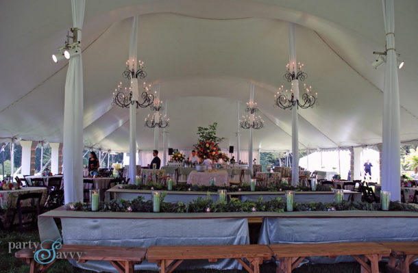 reception tent with benches and chandeliers